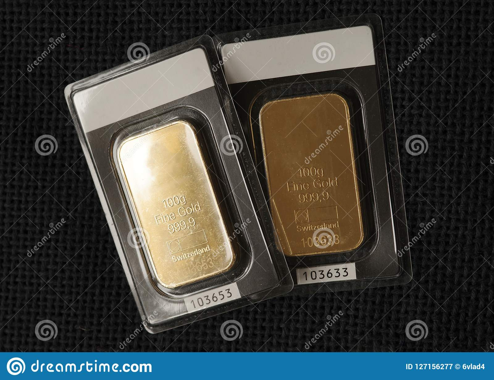 Two minted gold bars weighing 100 grams each against the background of a dark fabric texture