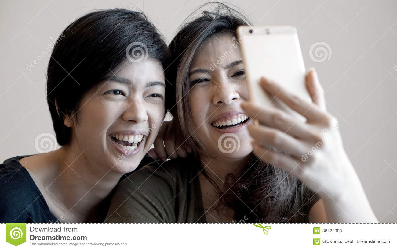 two mixed race asian girls taking selfie with smart phone stock