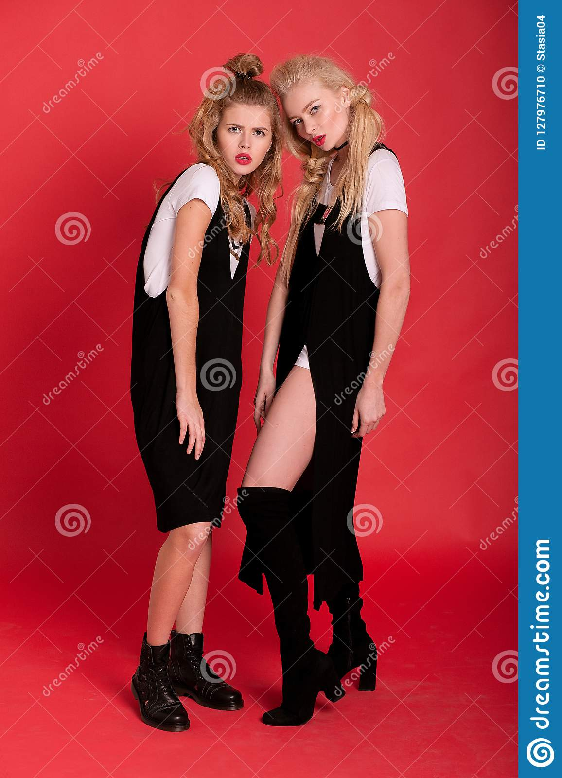 Two models in black dress and jackboots posing on red background