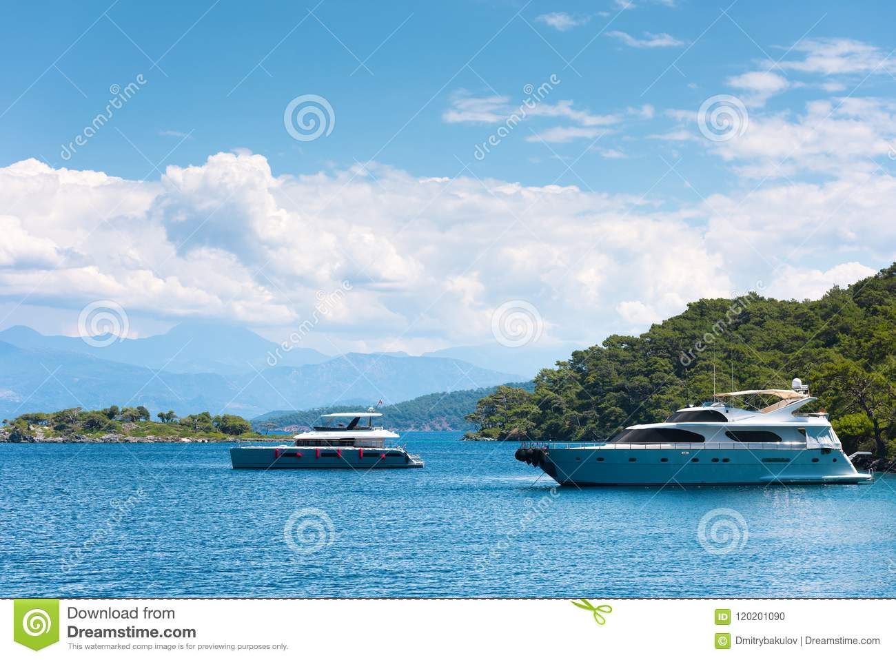 Two Modern Yachts In A Picturesque Sea Bay  The Island And
