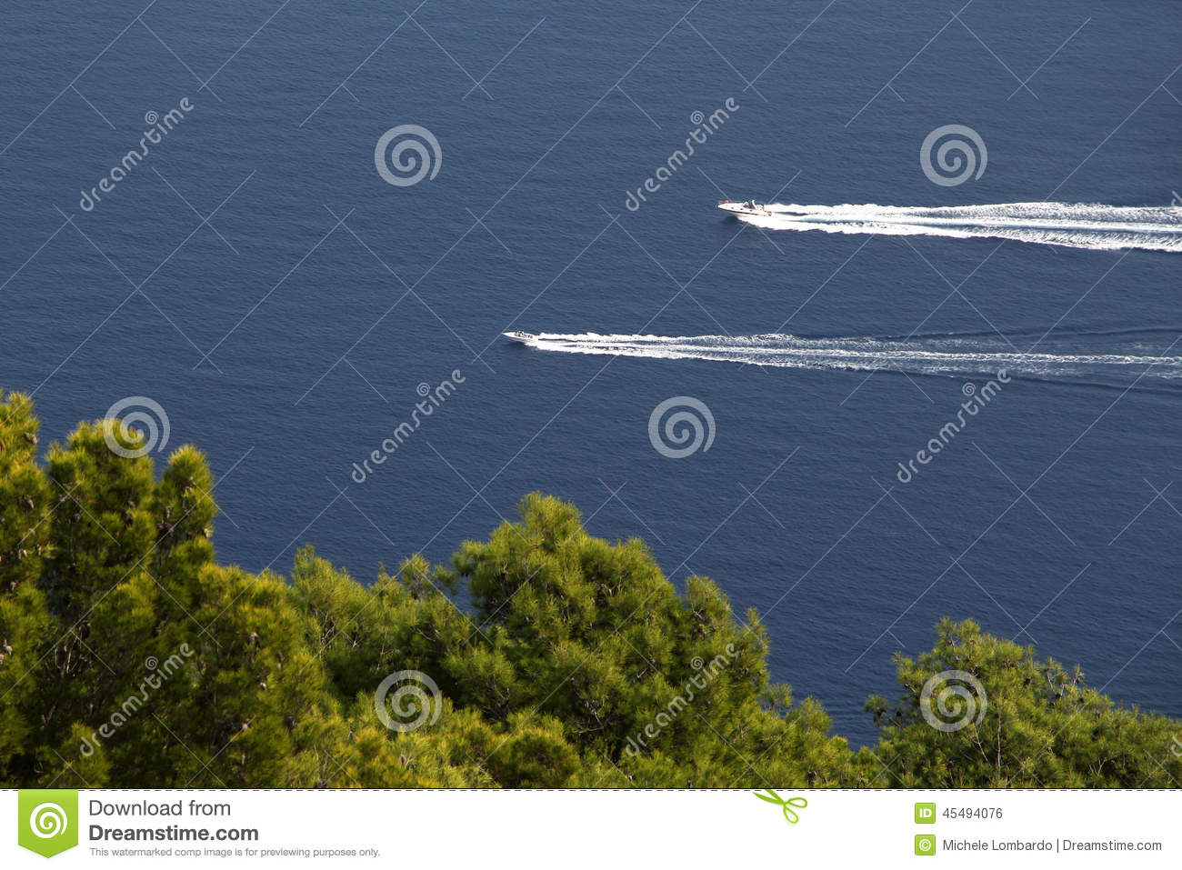 Two motorboats against a blue sea and trees