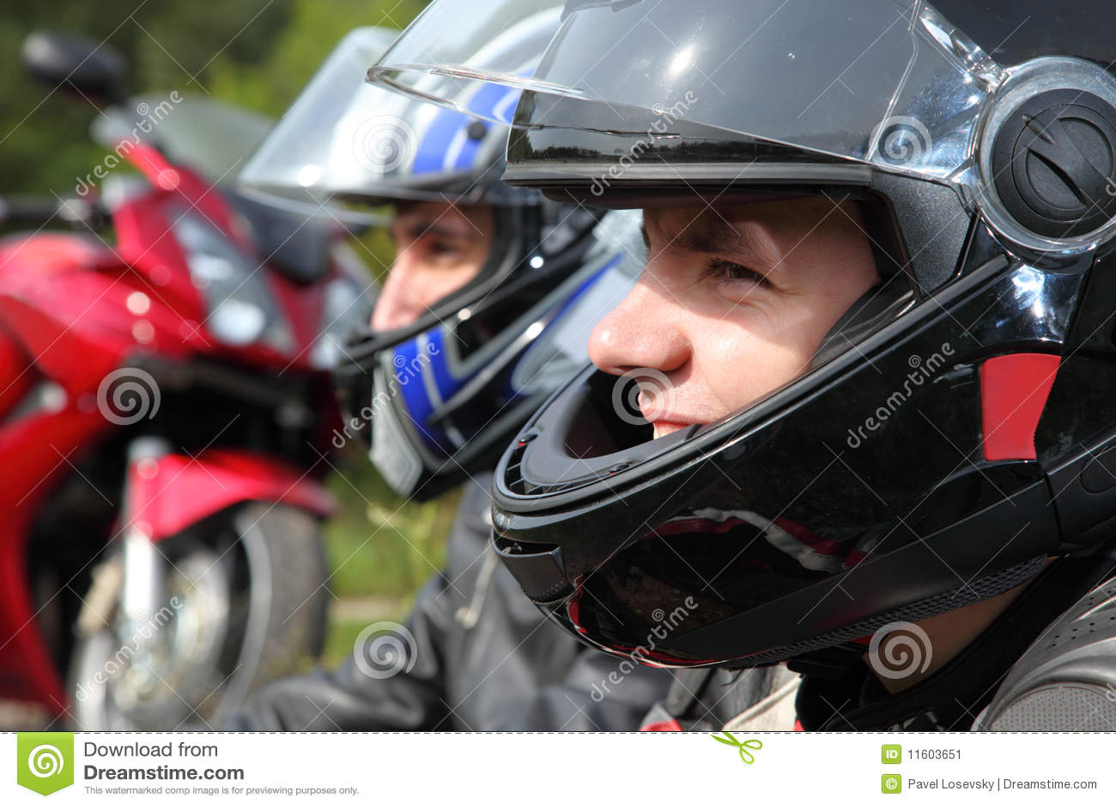 Two motorcyclists sitting near bike