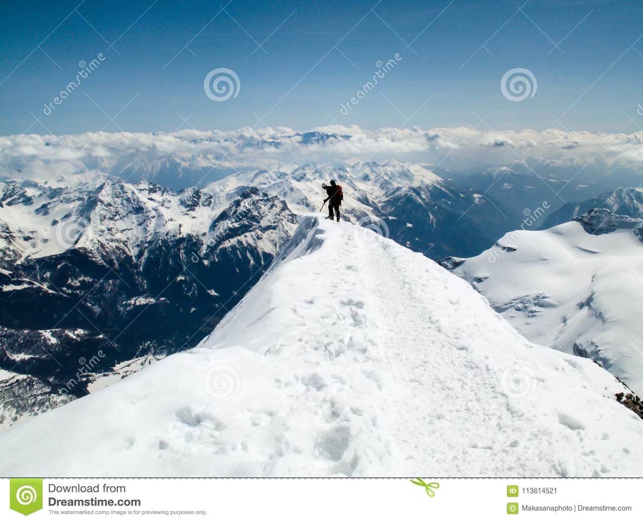 Two Mountain Climbers On A Narrow And Exposed Summit Ridge Lo Ng Over The Edge To See What Is Below