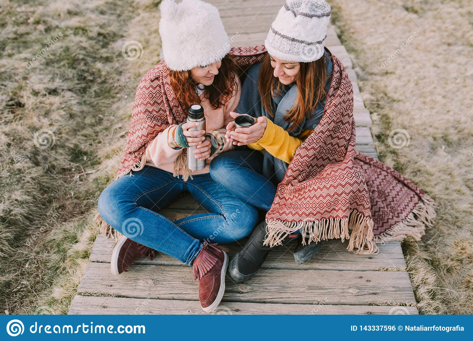 Two friends wrapped in a blanket are sitting in the meadow while they take out a thermos to prepare a broth