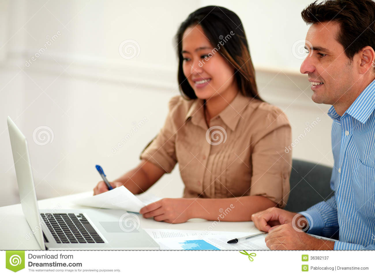 Two multi ethnic colleagues working on documents