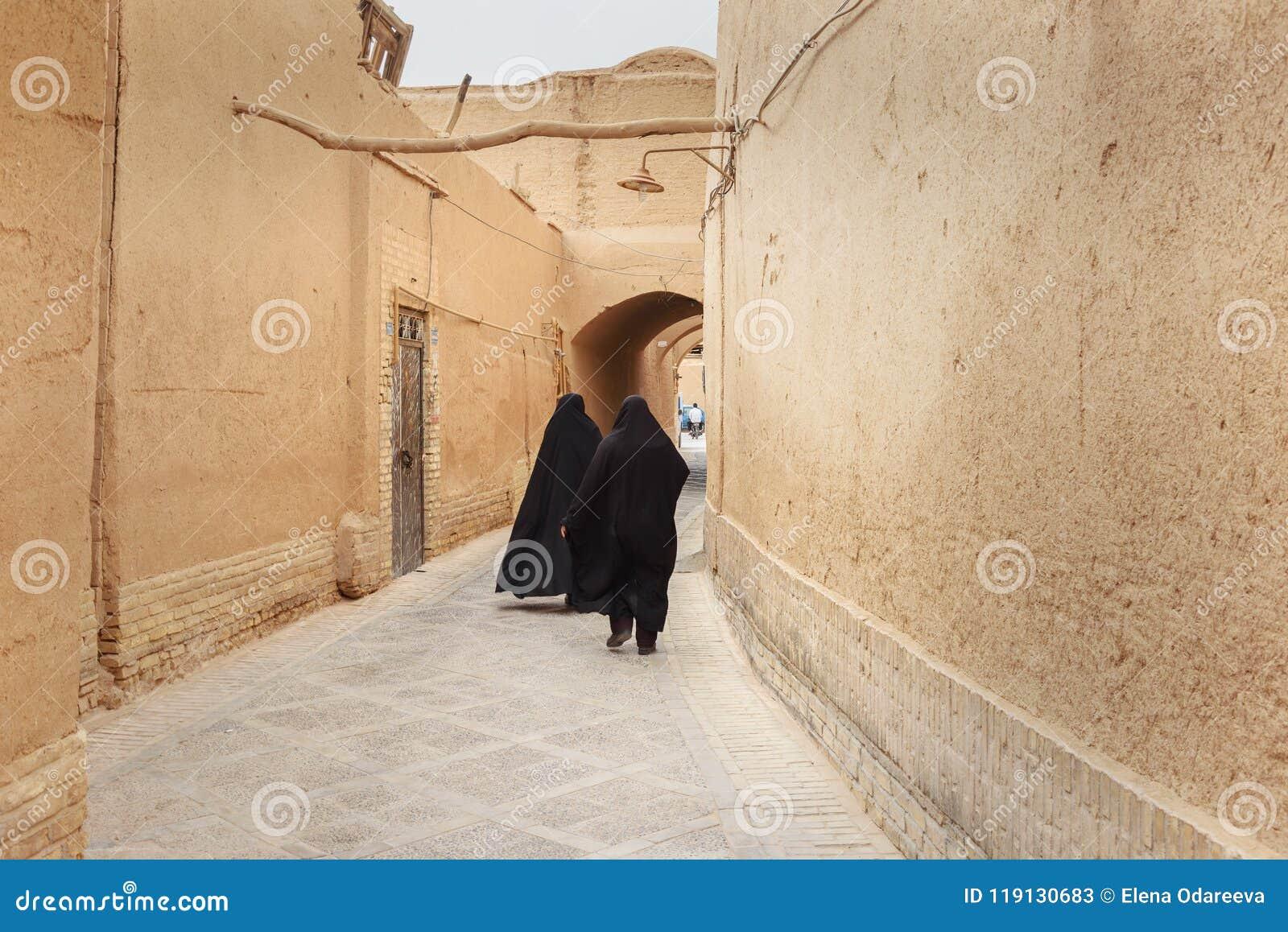 Two Muslim women, dressed in black chador walk on the narrow street of old town in Yazd. Iran