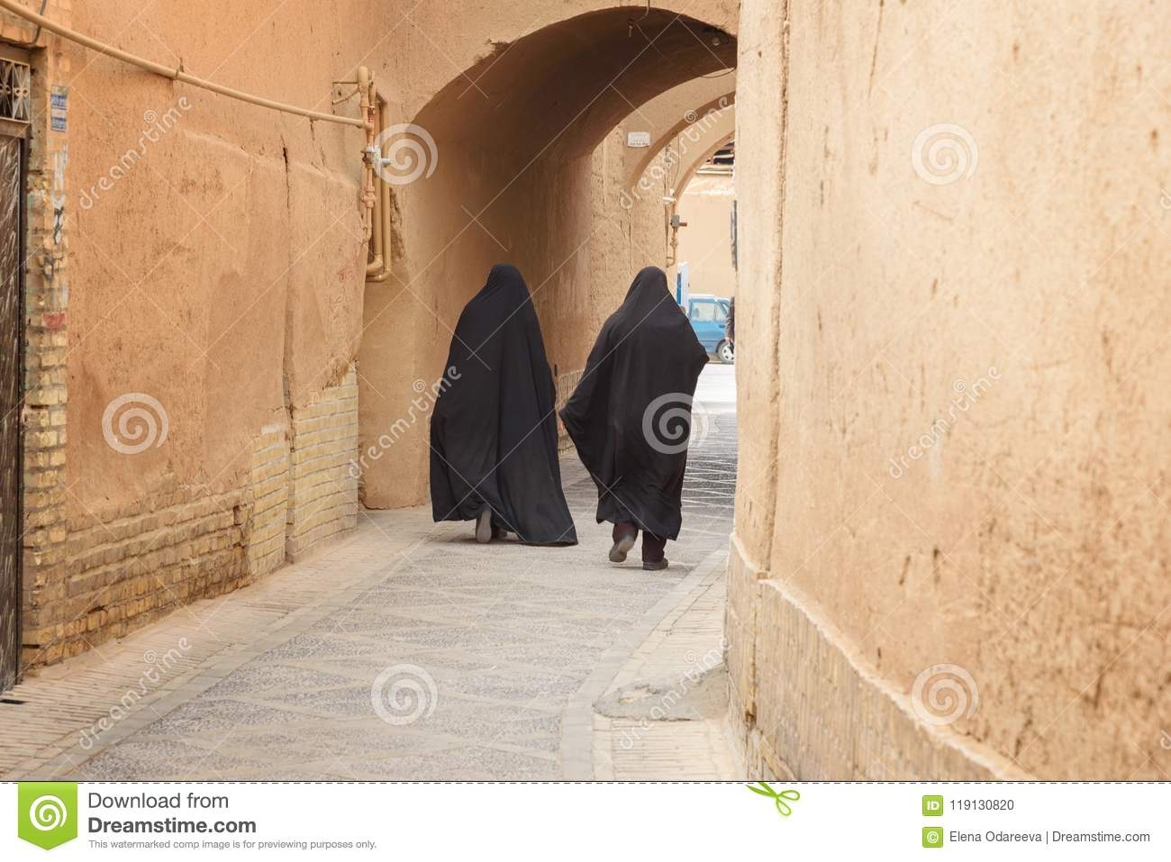 Two Muslim women, dressed in black chador walk on the narrow street of old town in Yazd. Iran