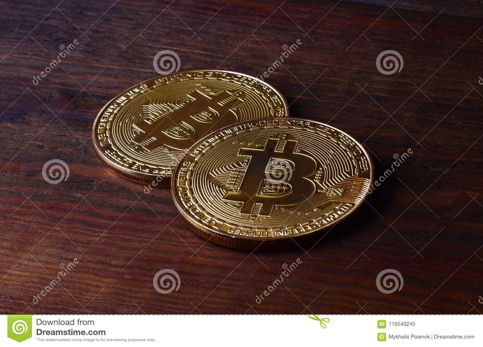 Two New Golden Physical Bitcoins Lies On Dark Wooden Backgound Close Up High Resolution