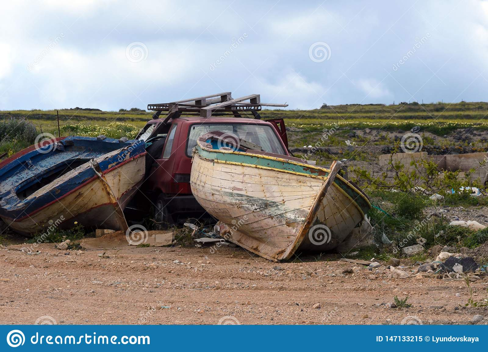 Two old abandoned fishing boats and a red wrecked car in a garbage dump. Abandoned things. Transport