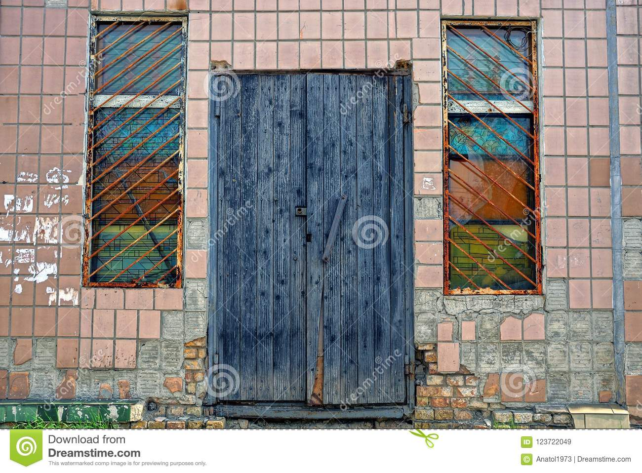 two old windows with a lattice and a gray wooden door on the wall of