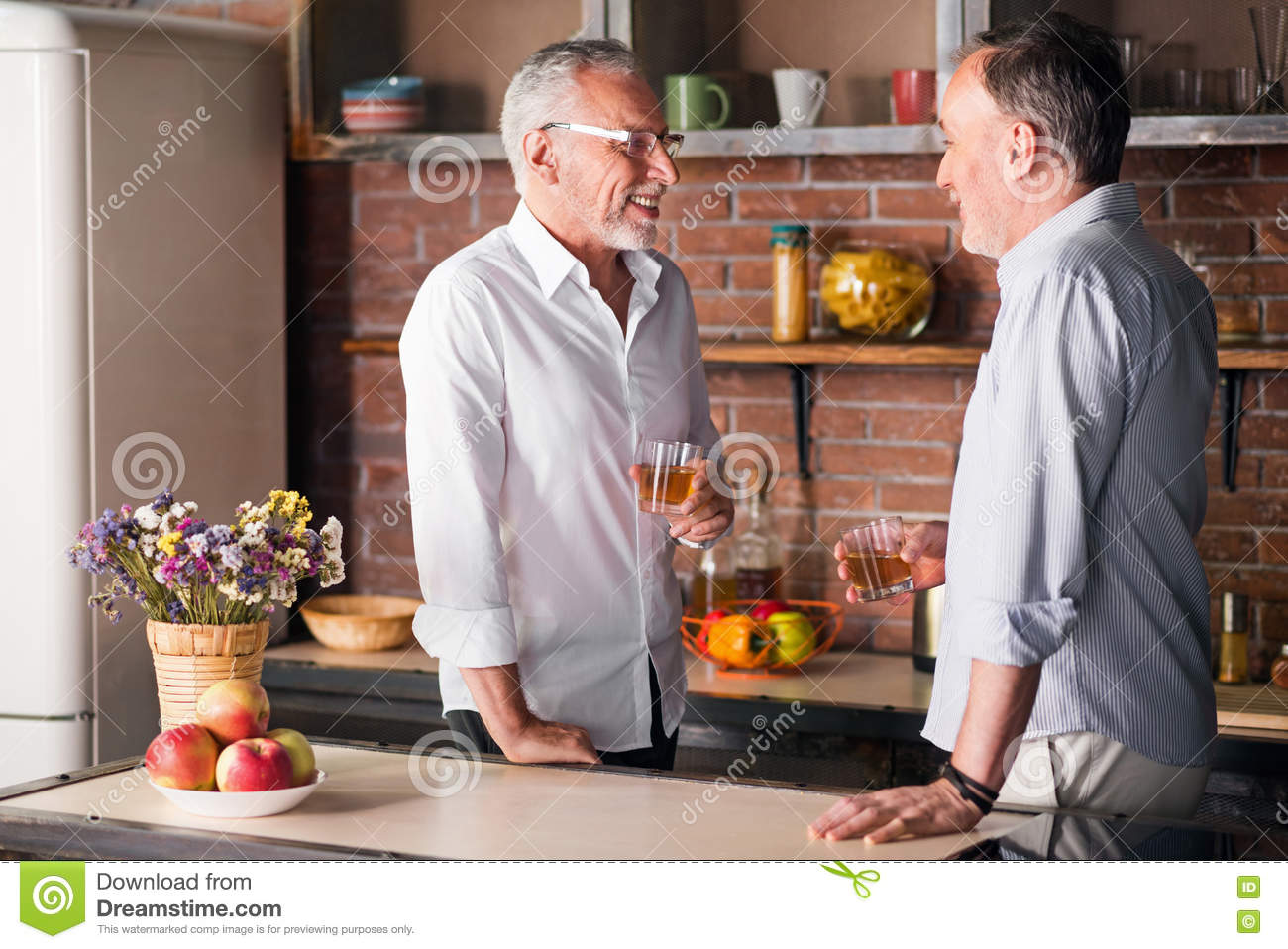 Two Old Male Friends Having Drinks In The Apartment Stock Photo