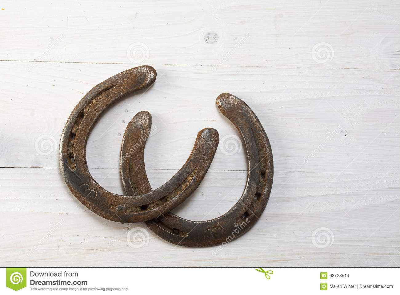 Two Old Rusty Horseshoes On White Painted Wood Symbol For Good
