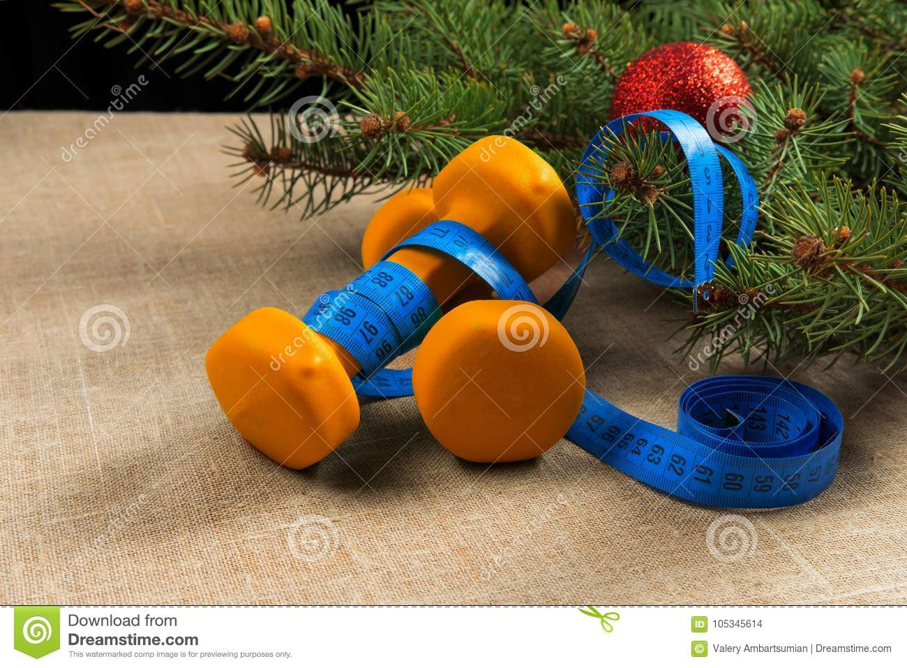 Christmas Sports Background.Two Orange Dumbbells Fitness Christmas Tree With Red New