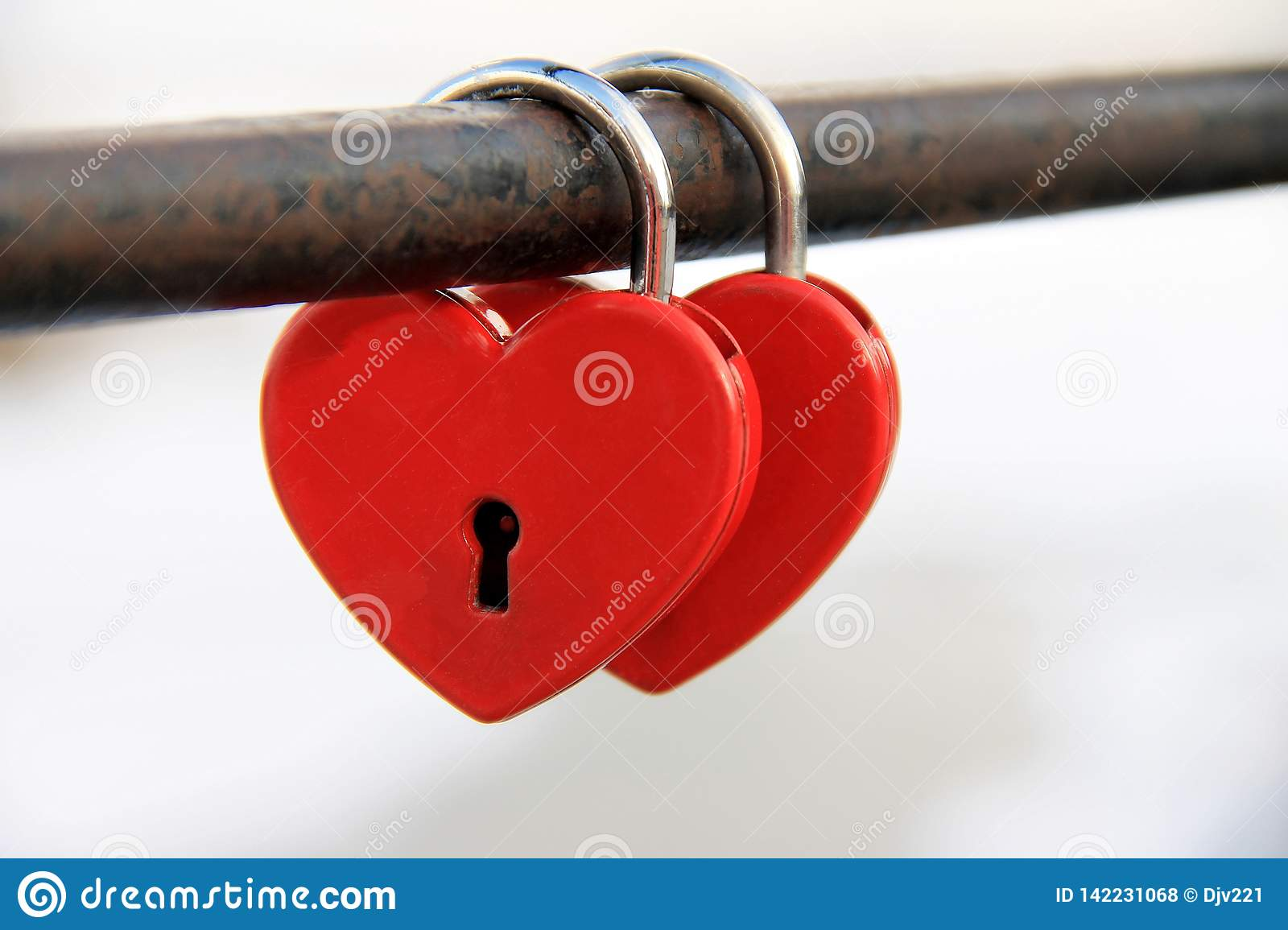 Two padlocks in the shape of hearts snapped onto the pipe