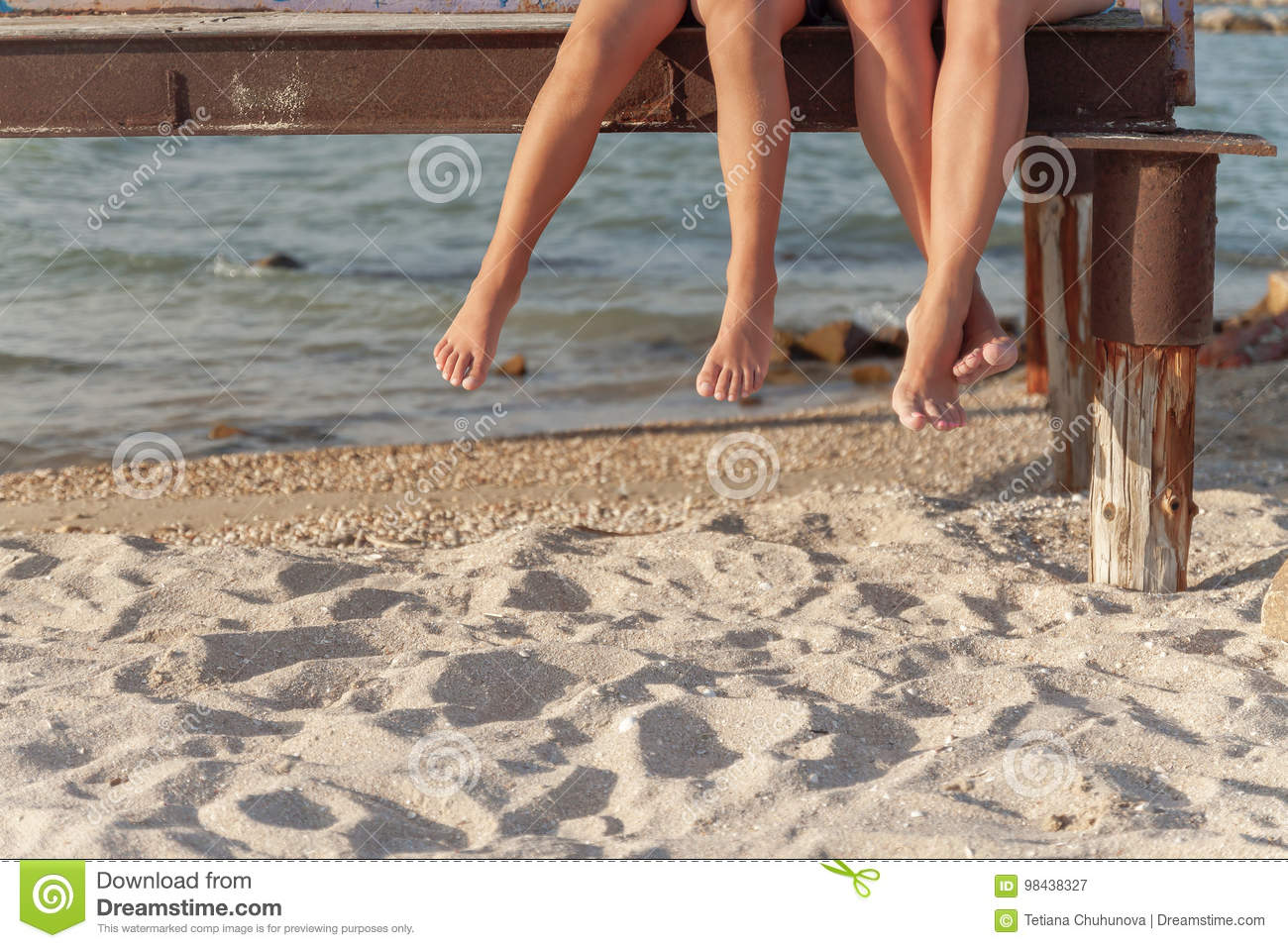 two pairs of legs dangling over the beach sand