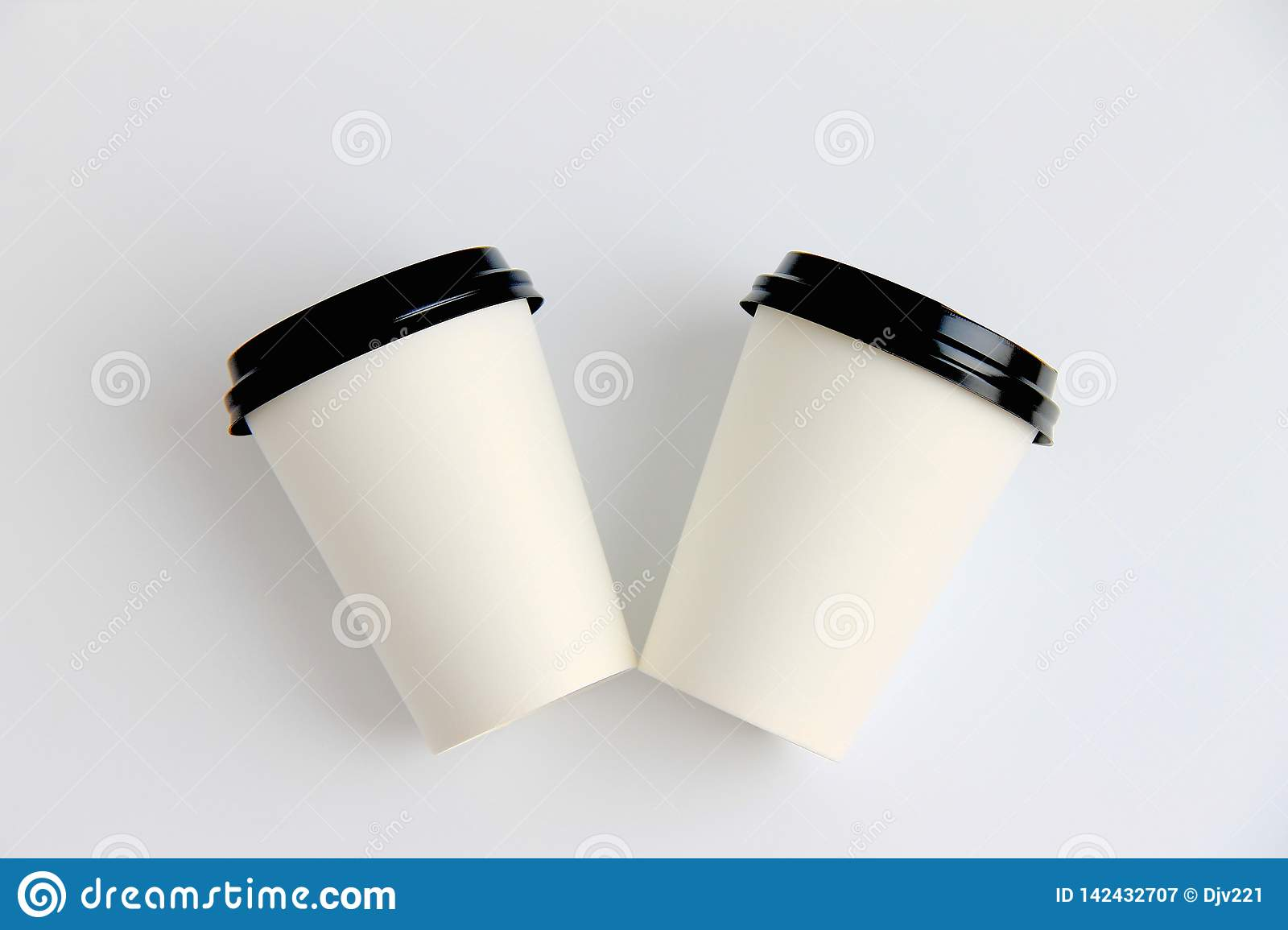 Two paper glasses with lids on a light background side view