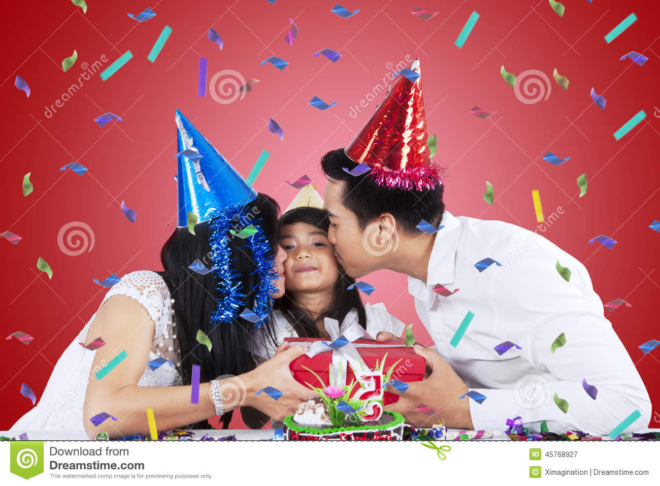 Portrait Of Asian Parents Kissing Their Child While Giving A Gift In Birthday Party