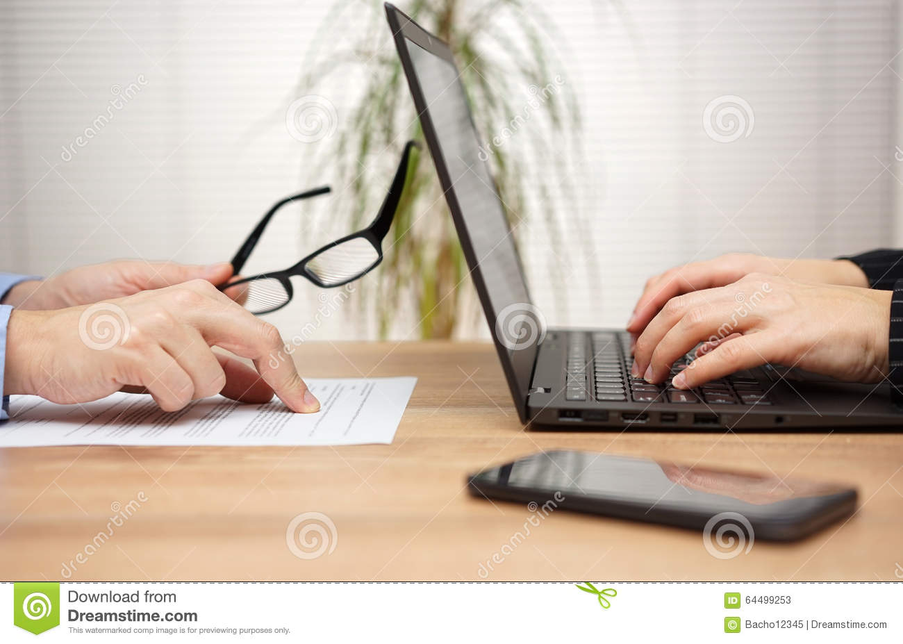 two partners are examining and reviewing document in office, woman is using laptop for comments