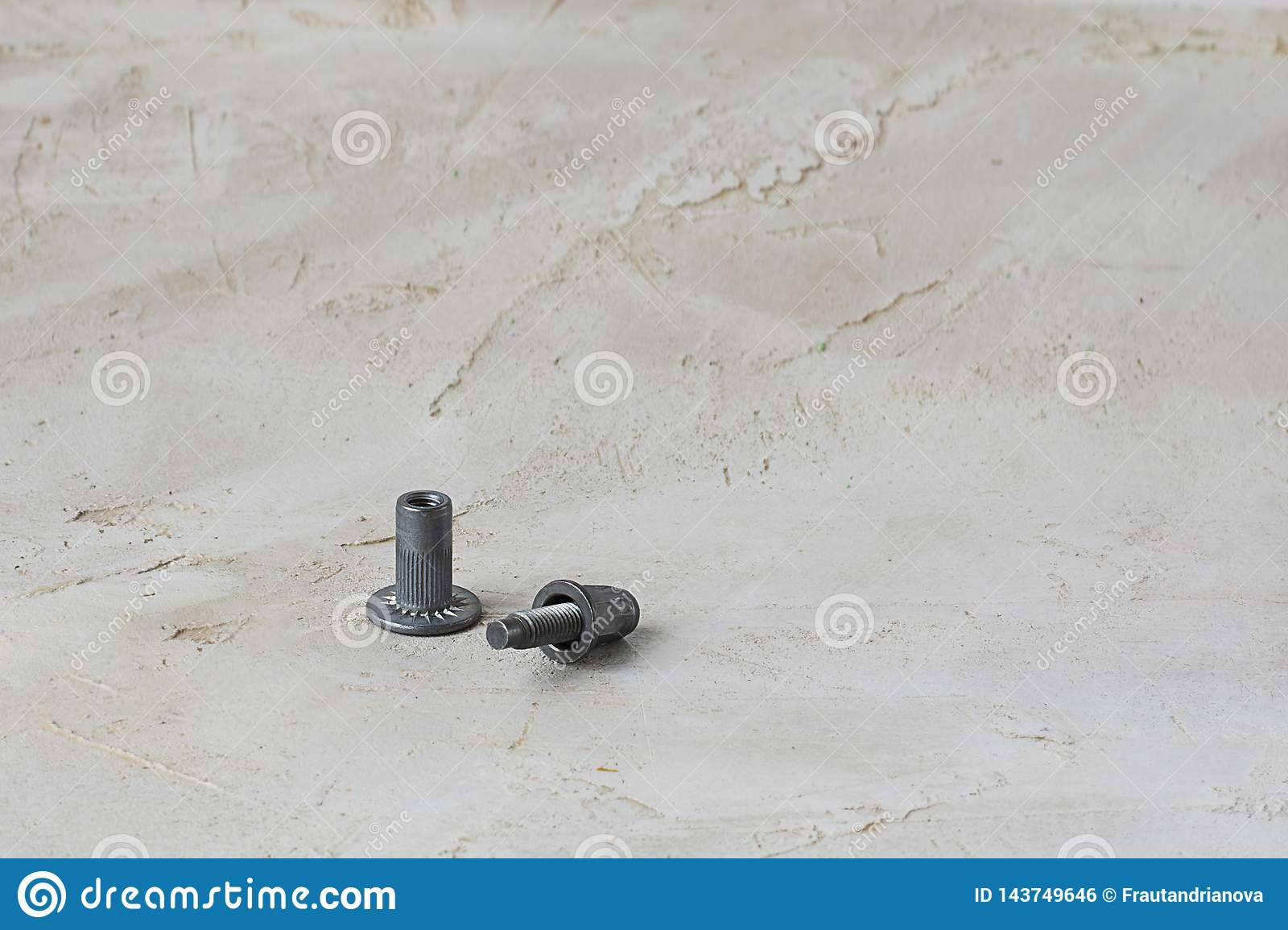 Two parts of metal pop Rivet fastener on grey cement background. Horizontal with copy space for text and design. Ingeneering