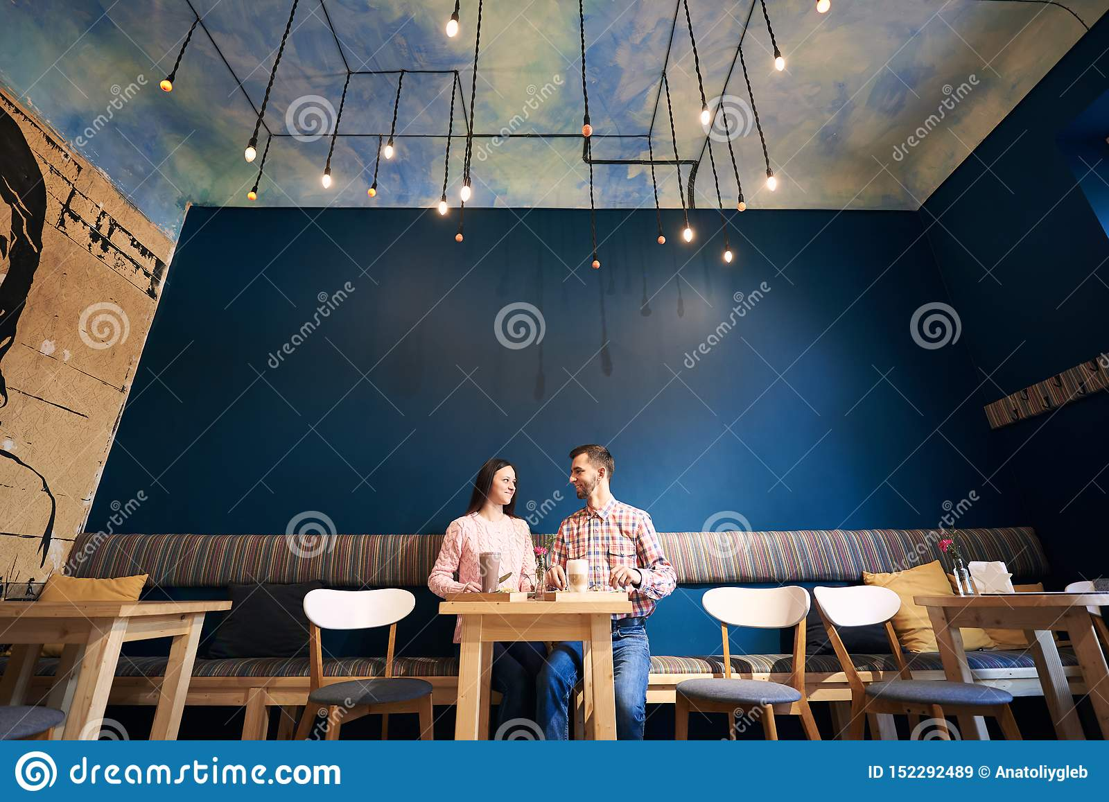 Two people in atmospheric cafe enjoying time spending with each other, having dinner, talking in cafe. Blue background.