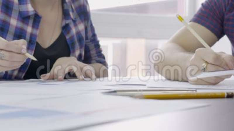 two people draw a drawing on ruler with a pencil on the desktop
