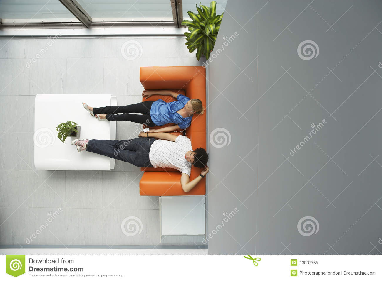 Two People Reclining On Orange Sofa At Office Royalty Free