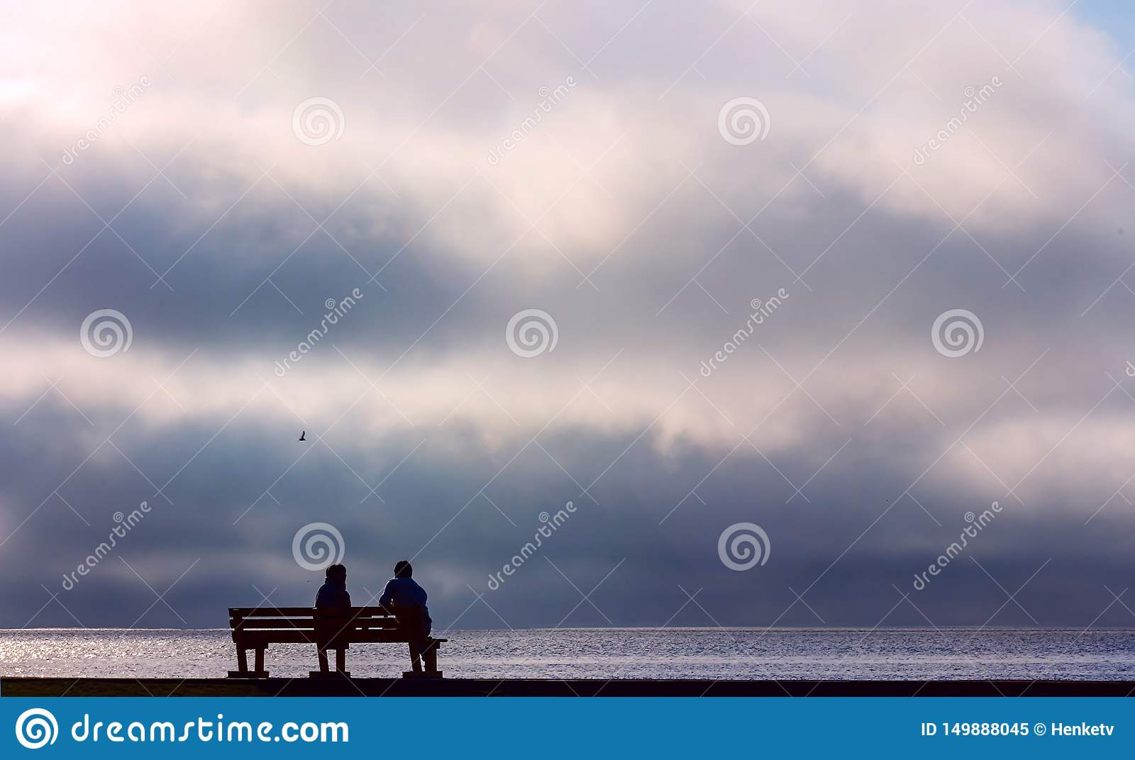Two people sitting on a street bench and watching the dramatic sunset