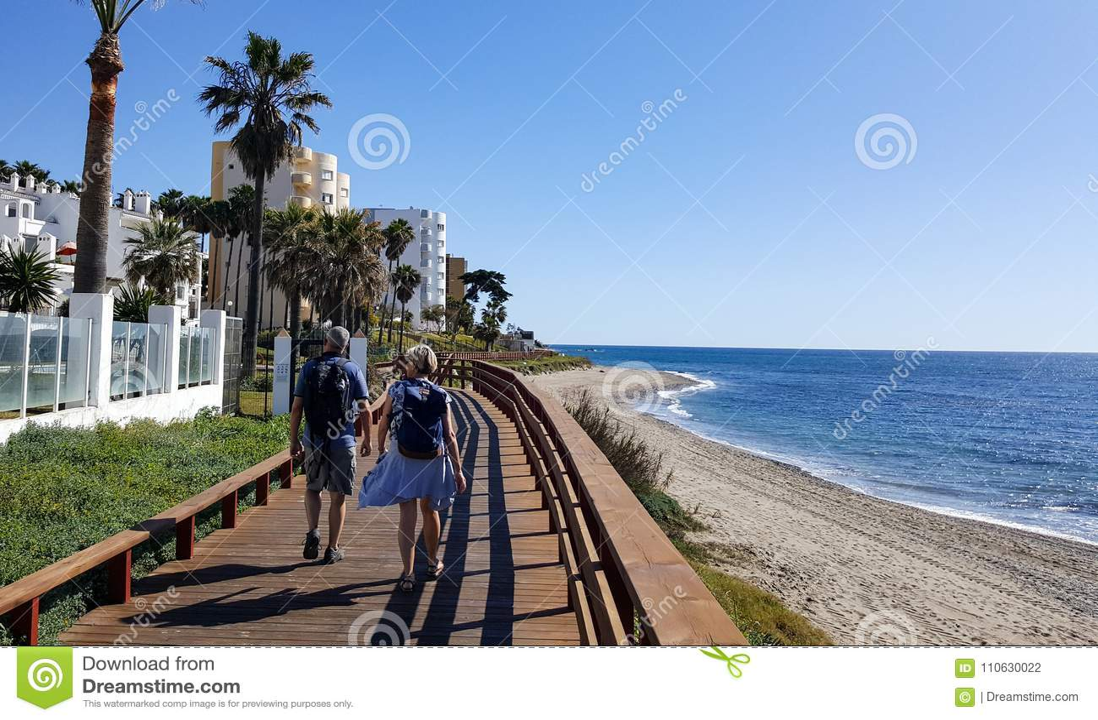 Two people walking on the coast of Mediterranean