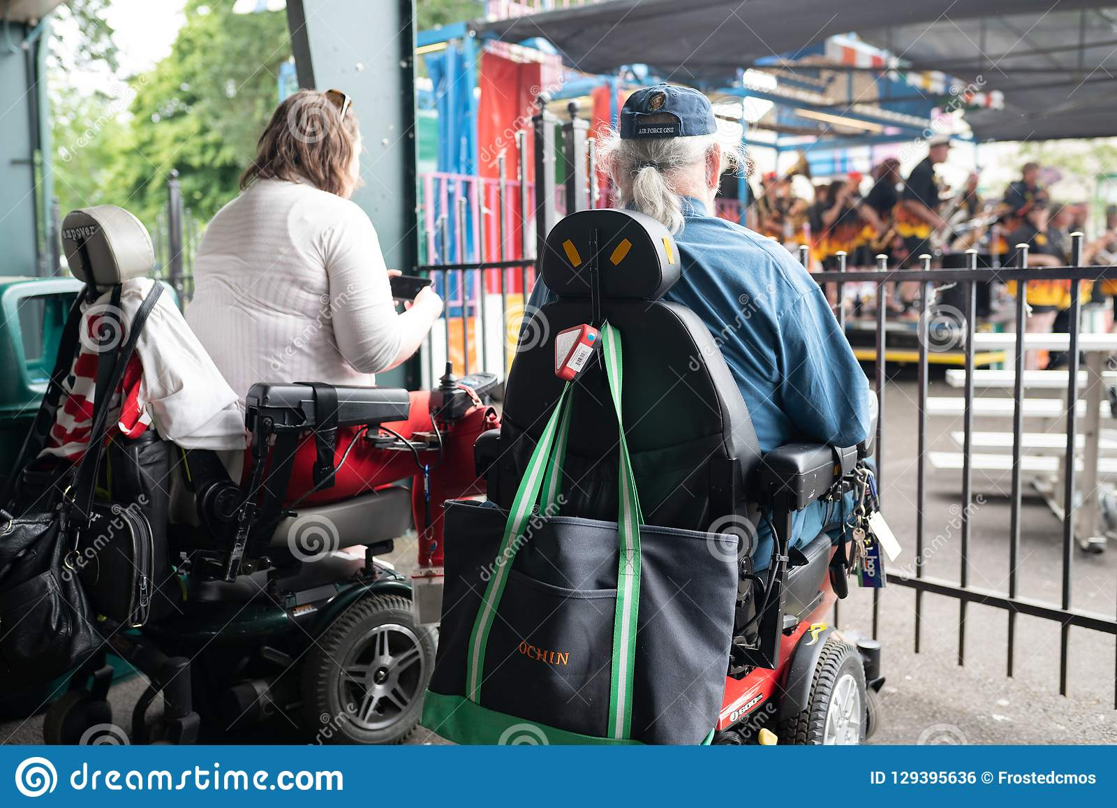 Two people on wheelchairs enjoying the outdoors concert