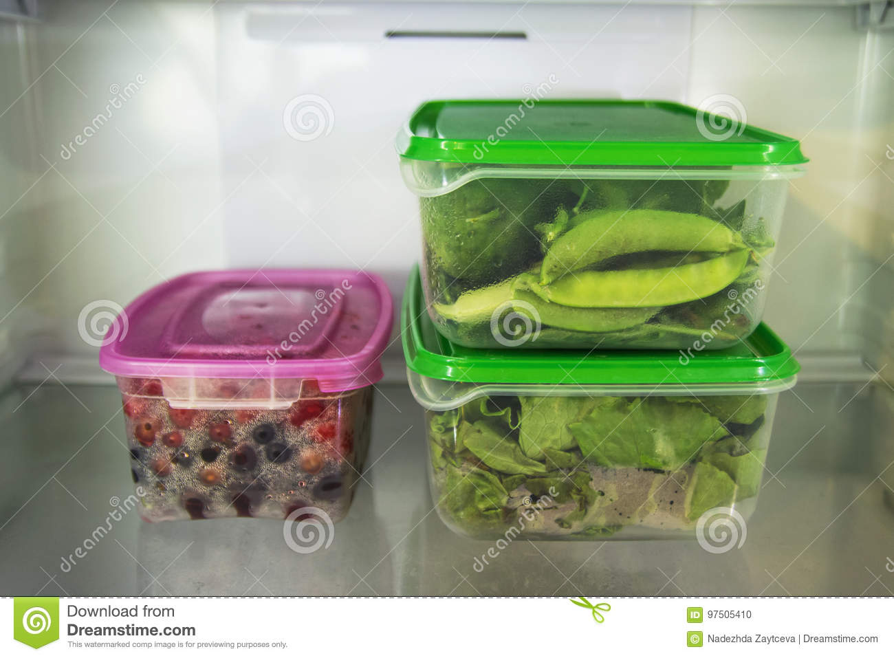 Two plastic food containers with green vegetable and one with berries on a shelf of a fridge.