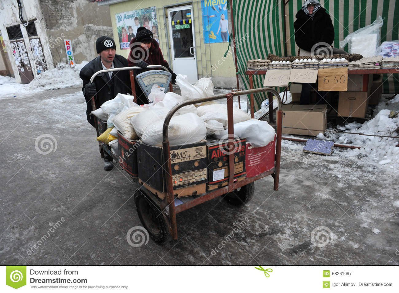 two porters carry a cart on the street with food editorial photography image 68261097. Black Bedroom Furniture Sets. Home Design Ideas