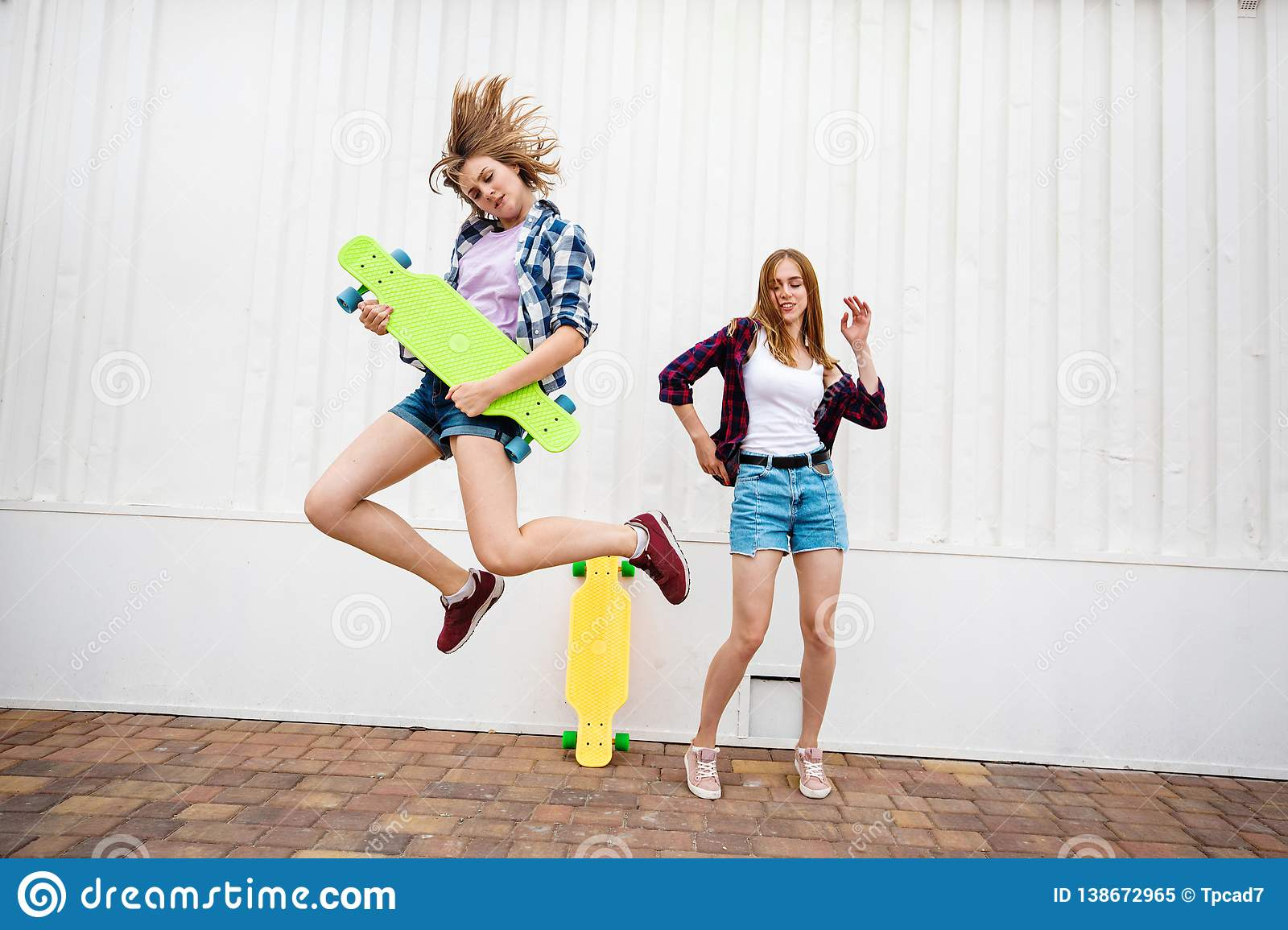 Two pretty blond girls wearing checkered shirts and denim shorts are jumping and dancing with bright longboards. Young