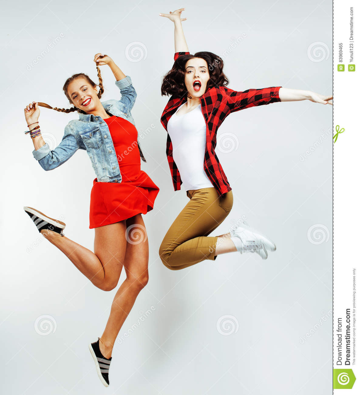 Two pretty brunette and blonde teenage girl friends jumping happy smiling on white background, lifestyle people concept