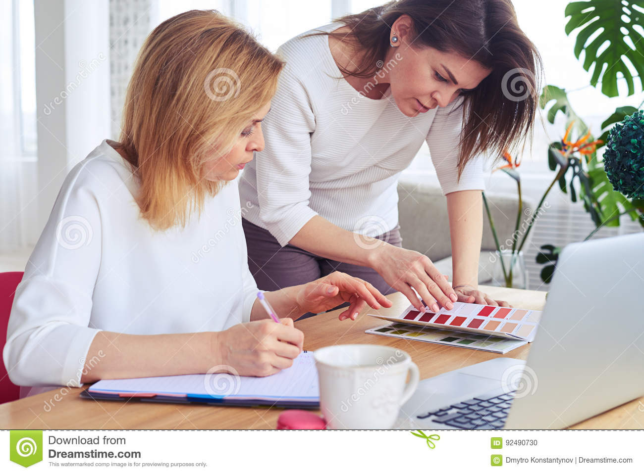 Two pretty businesswomen looking through catalog of color palett
