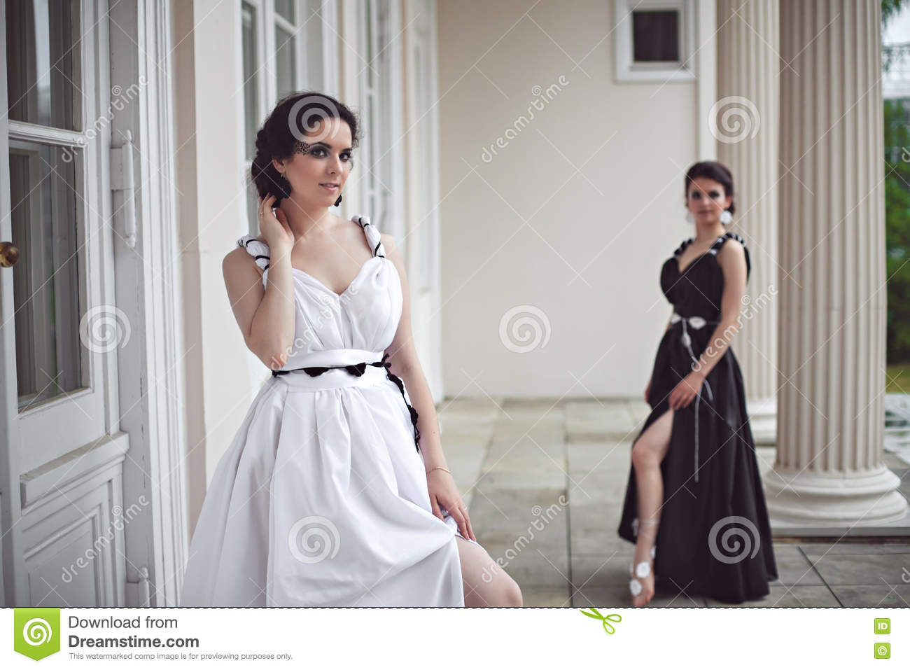 two pretty girls in black and white long dresses stock photo