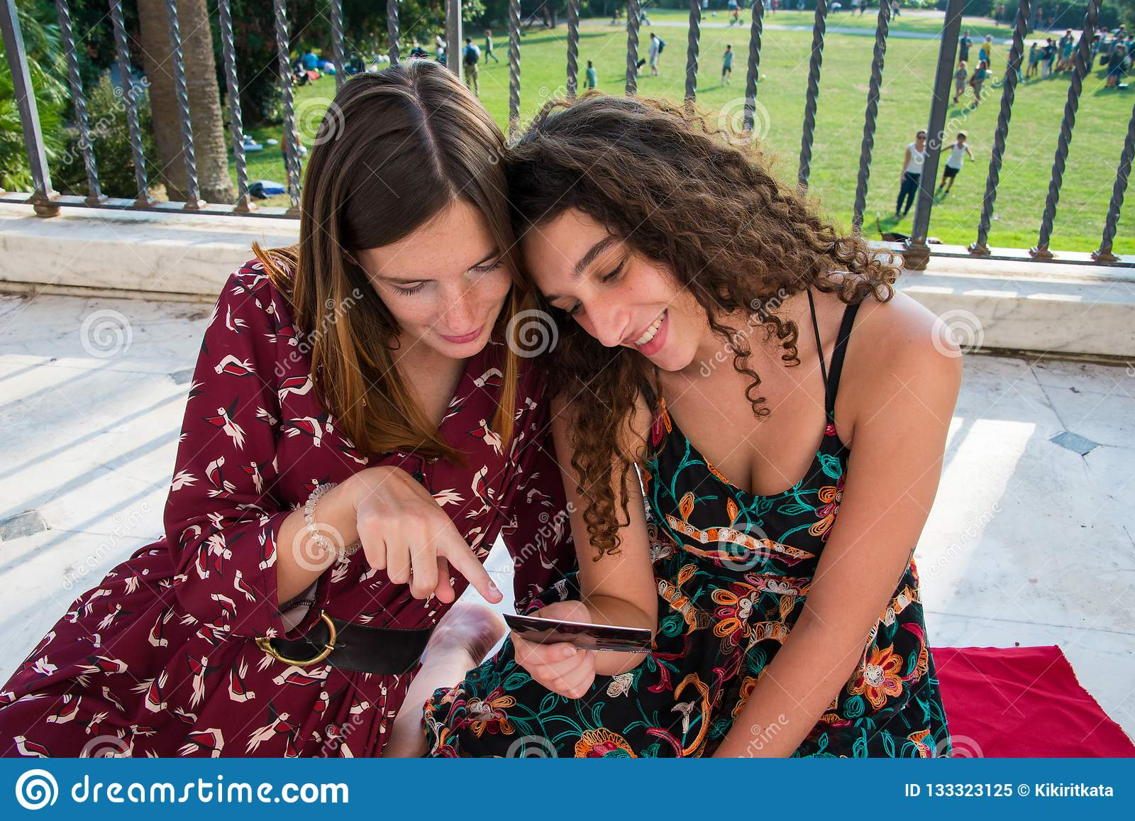 Two pretty girls are choosing photos for social media.