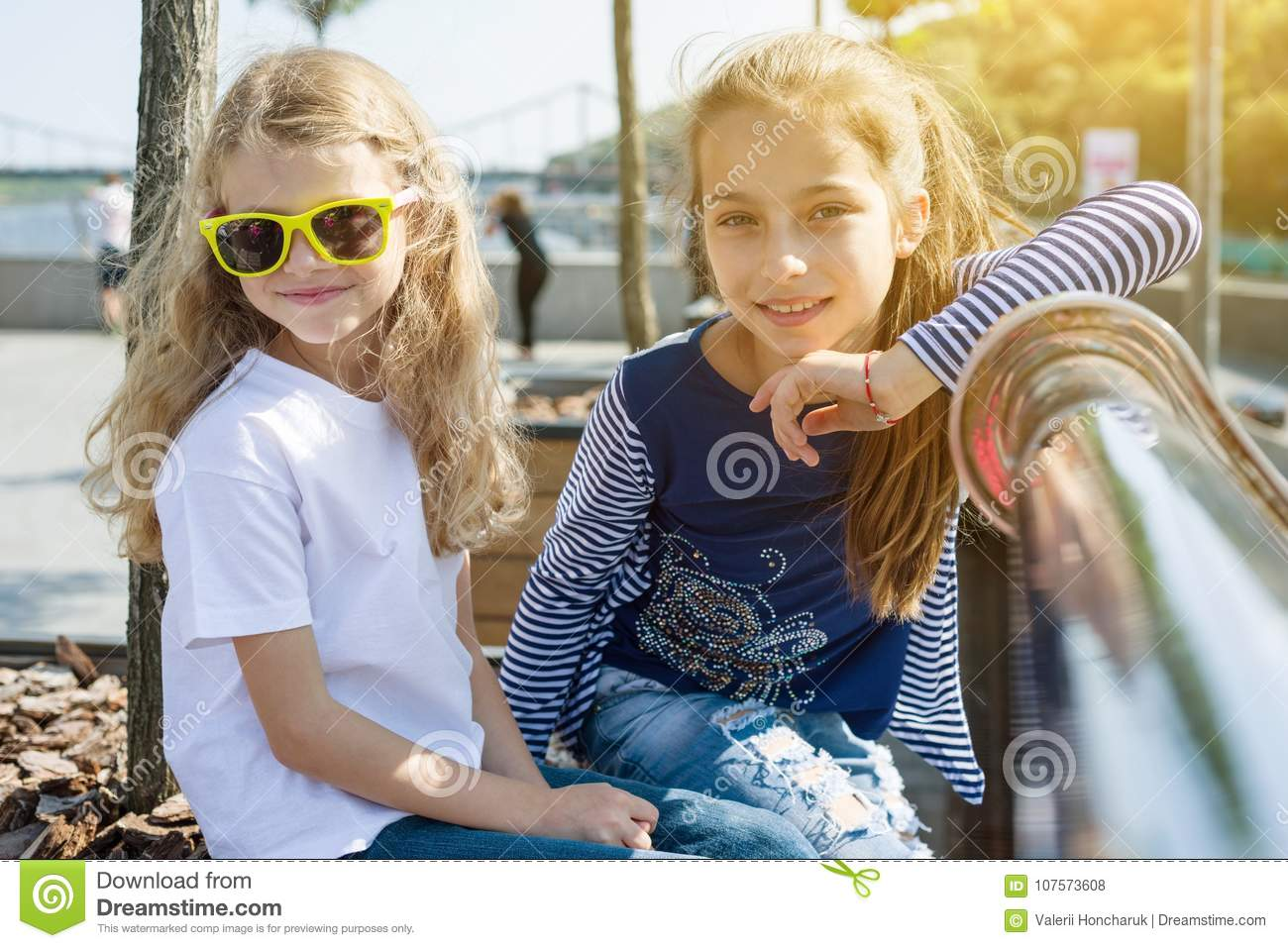 Two pretty little girls are looking at the camera and smiling.