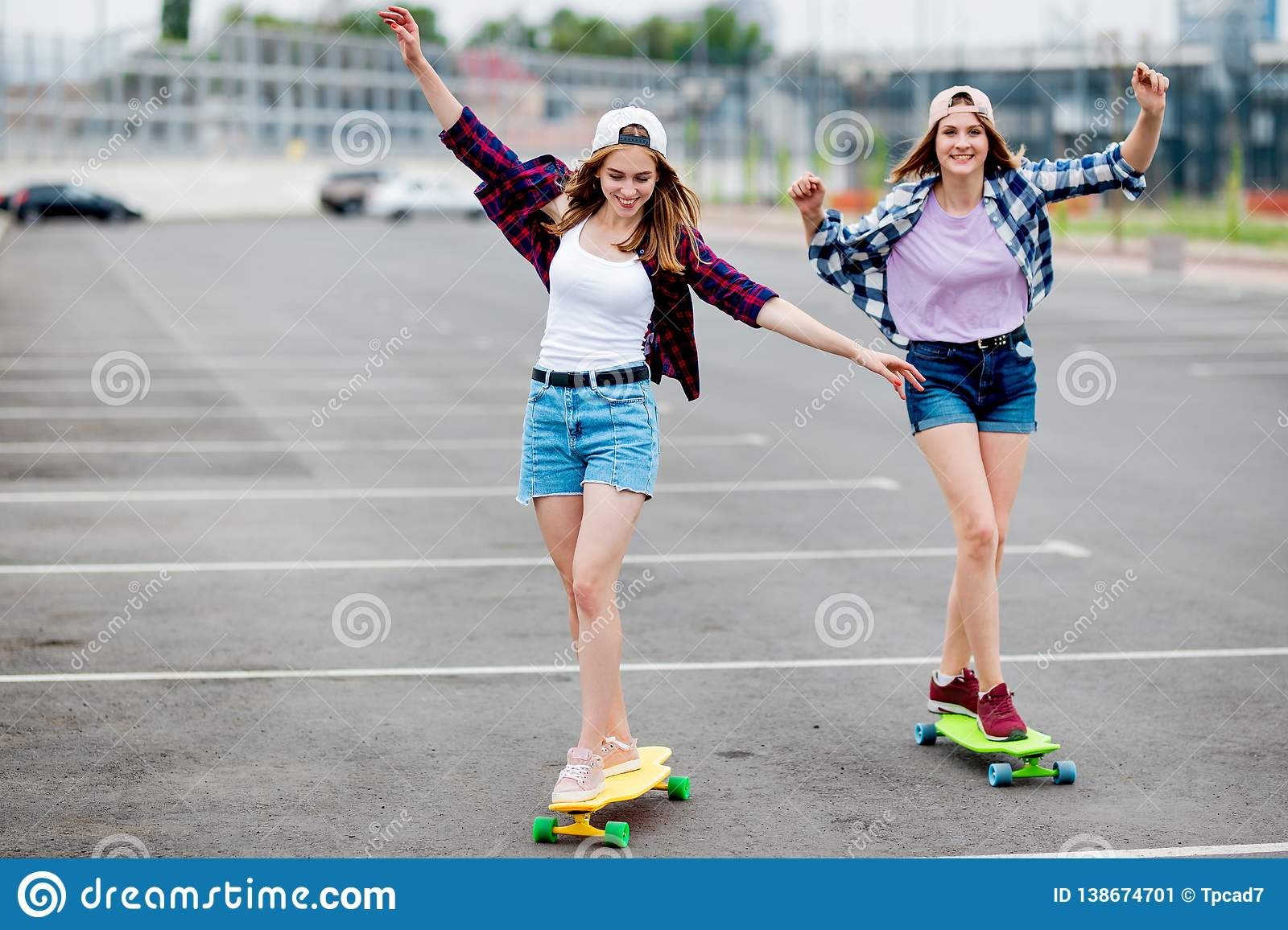 Two pretty smiling blond girls wearing checkered shirts, caps and denim shorts are longboarding on the empty car park