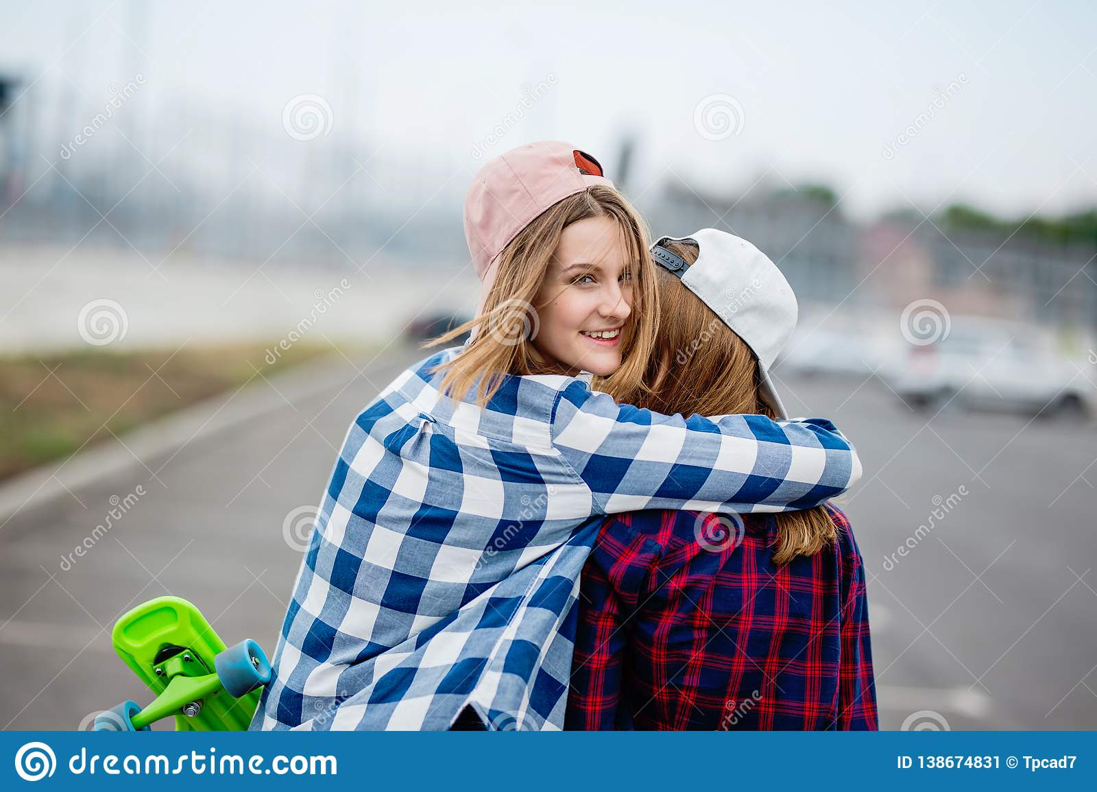 Two pretty smiling blond girls wearing checkered shirts, caps and denim shorts are standing and hugging on the empty car