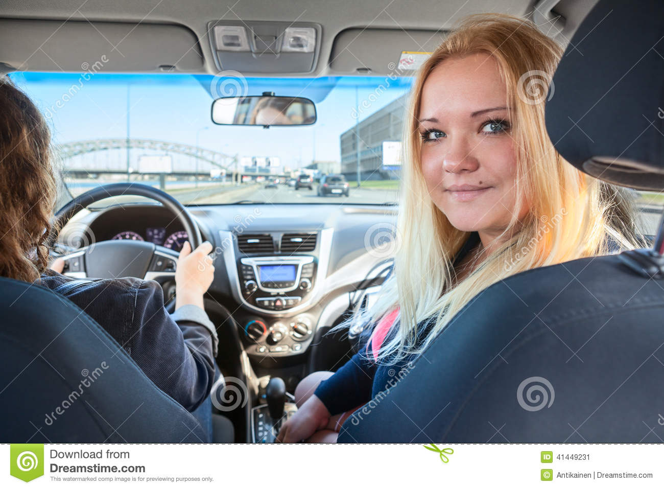 Two Pretty Woman Driving Car Blonde Passenger Looking