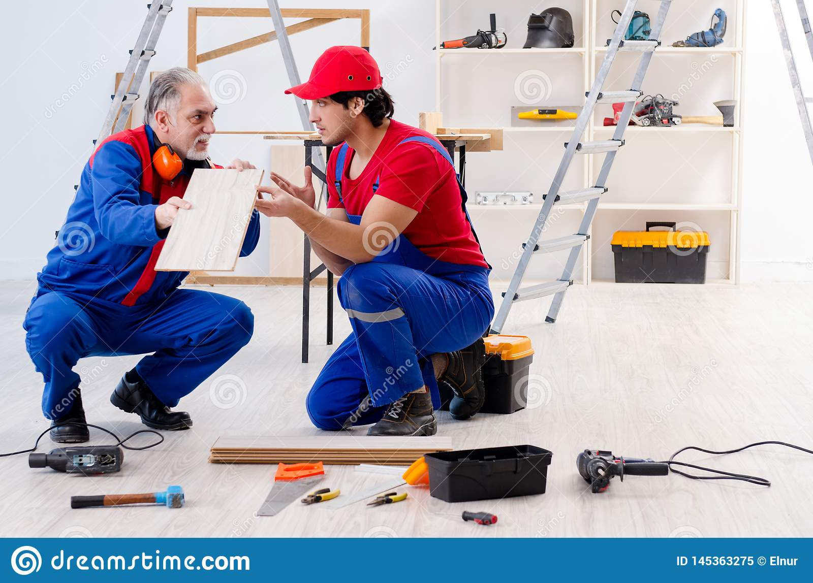 The Two Professional Contractors Laying Flooring At Home Stock