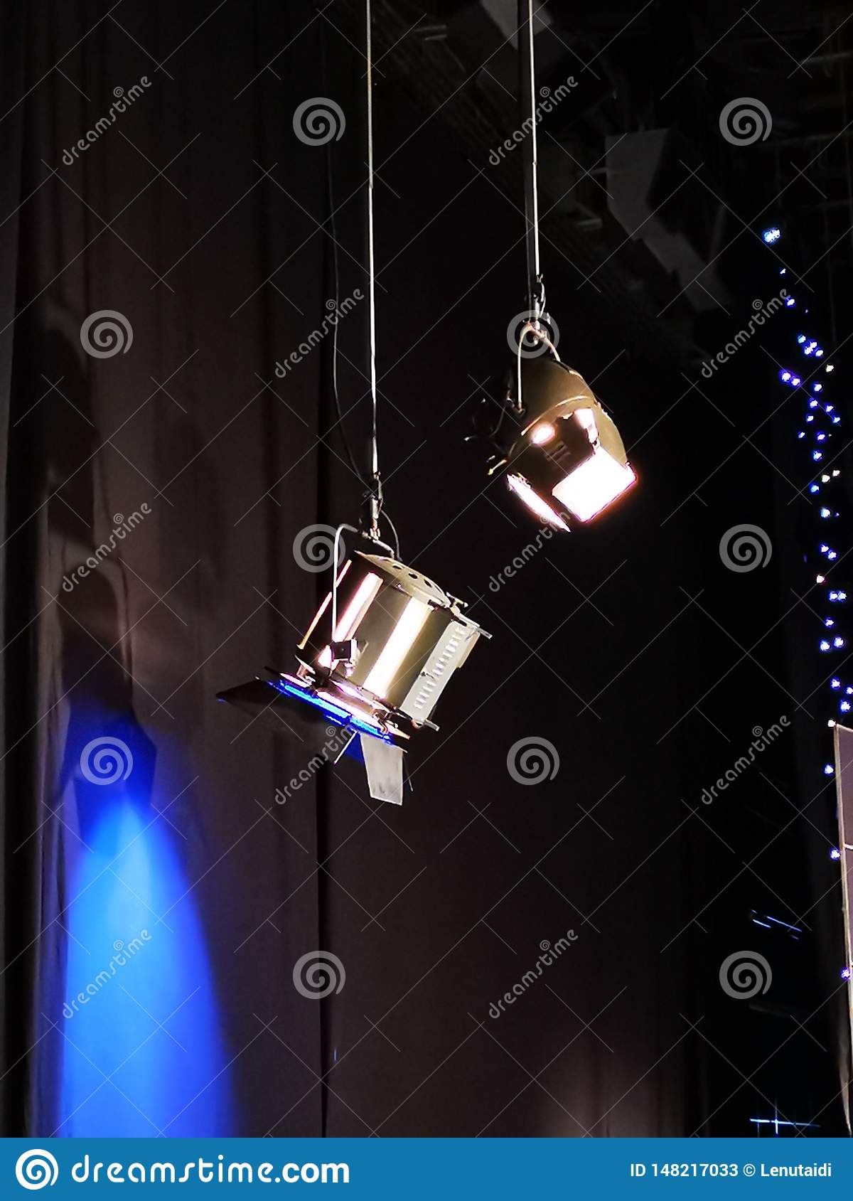 Two projectors lit in a television studio - one with a blue filter