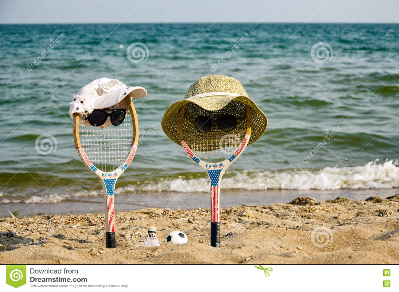 Two rackets (boy&girl) rest on the beach