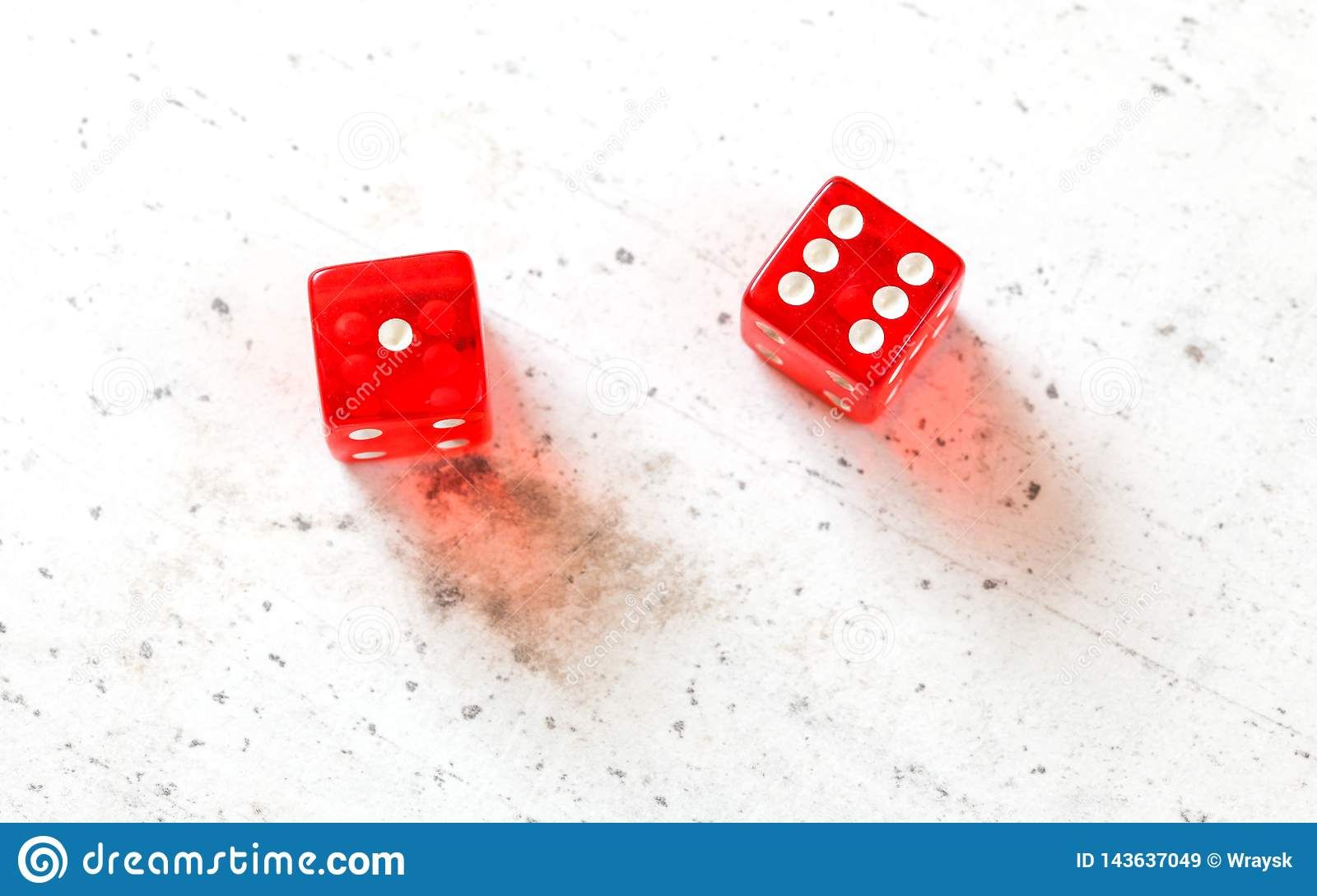 Two red craps dices showing Natural or Seven Out number 1 and 6 overhead shot on white board