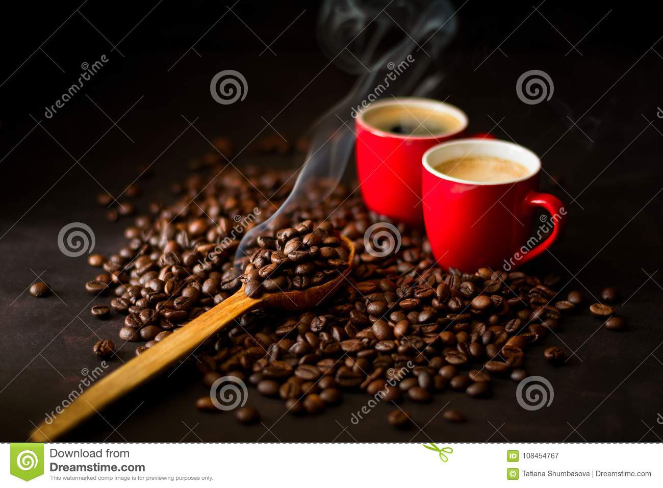 Two red cups of espresso with coffee beans on dark wooden background.