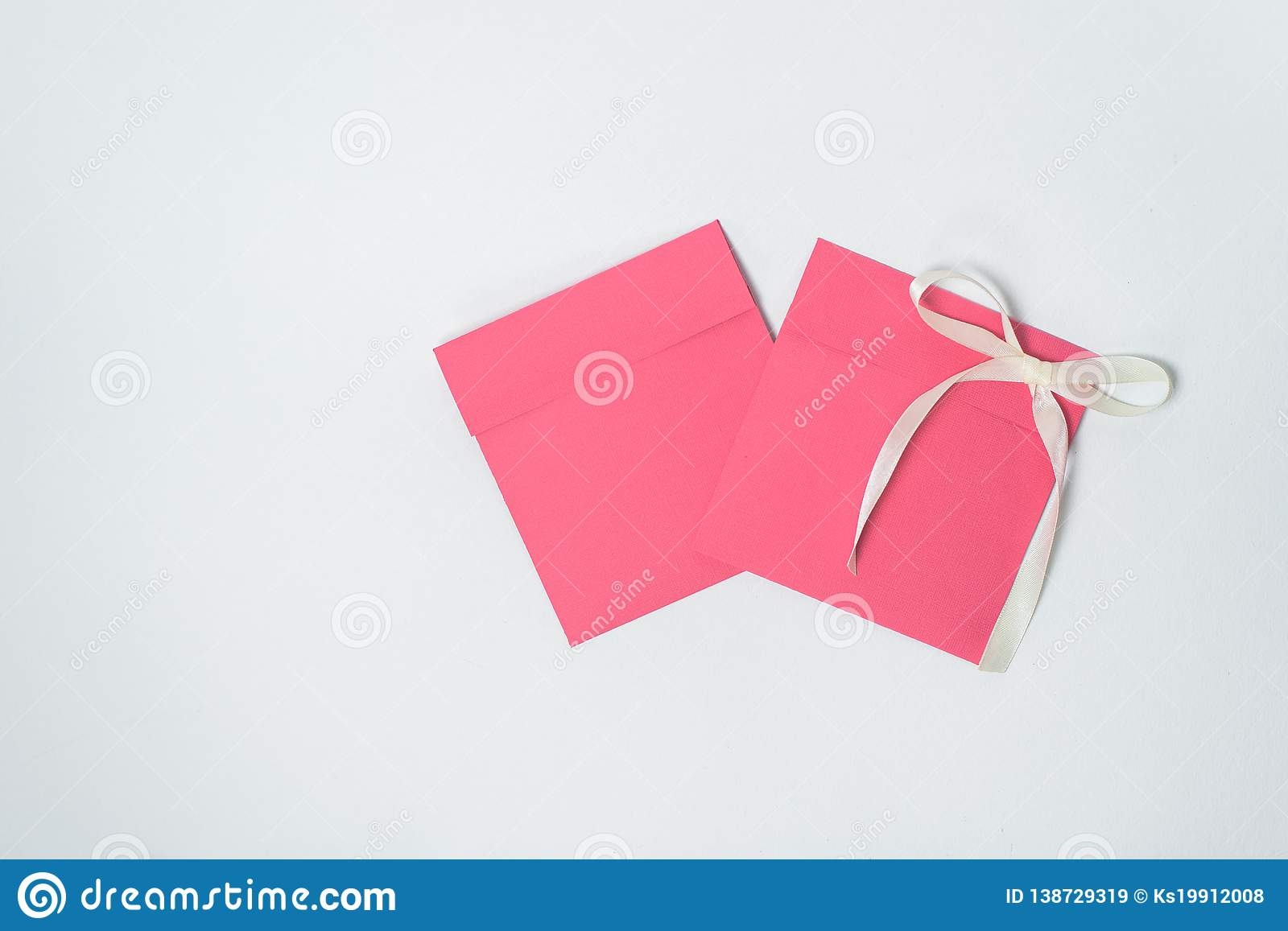 Two red envelope with yellow ribbon in the shape of a bow for CD, square envelope