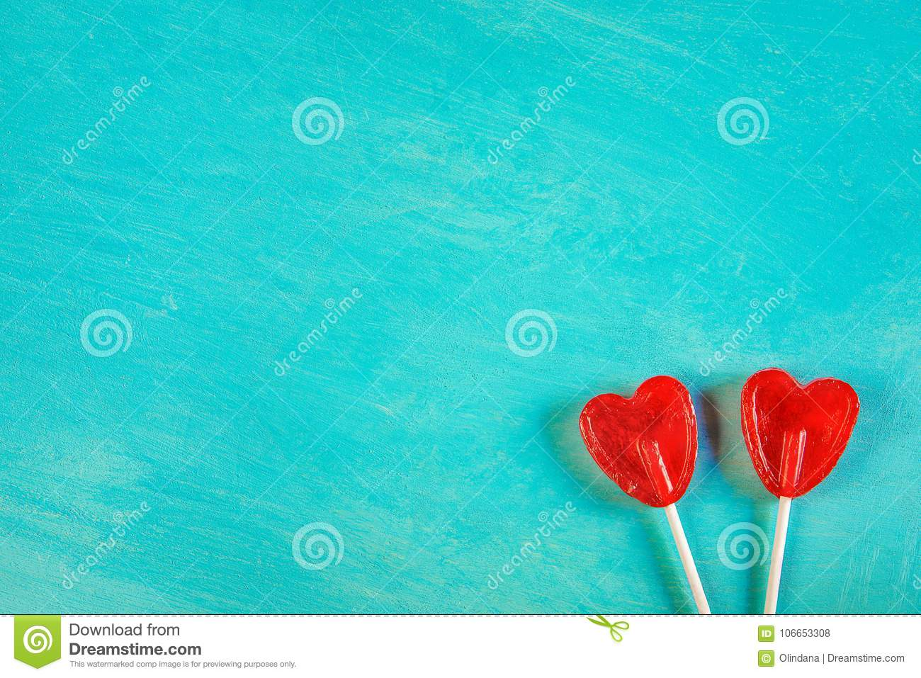 Two Red Heart Shape Candy Lollipops On Sticks On Turquoise