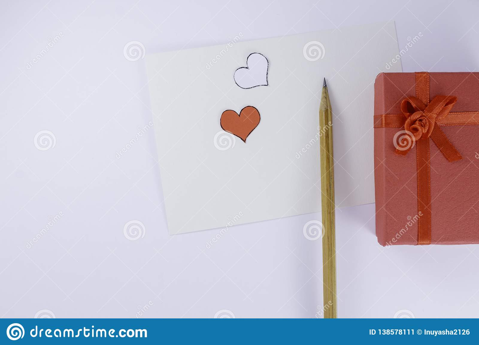 Two red and white hearts and wooden pencil near on empty letter with gift box on white background Valentine`s day