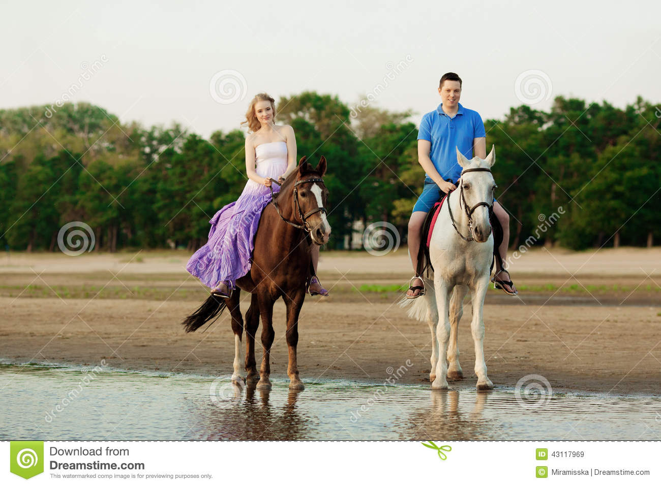 Two riders on horseback at sunset on the beach. Lovers ride horseback. Young beautiful man and woman with a horses at the sea.