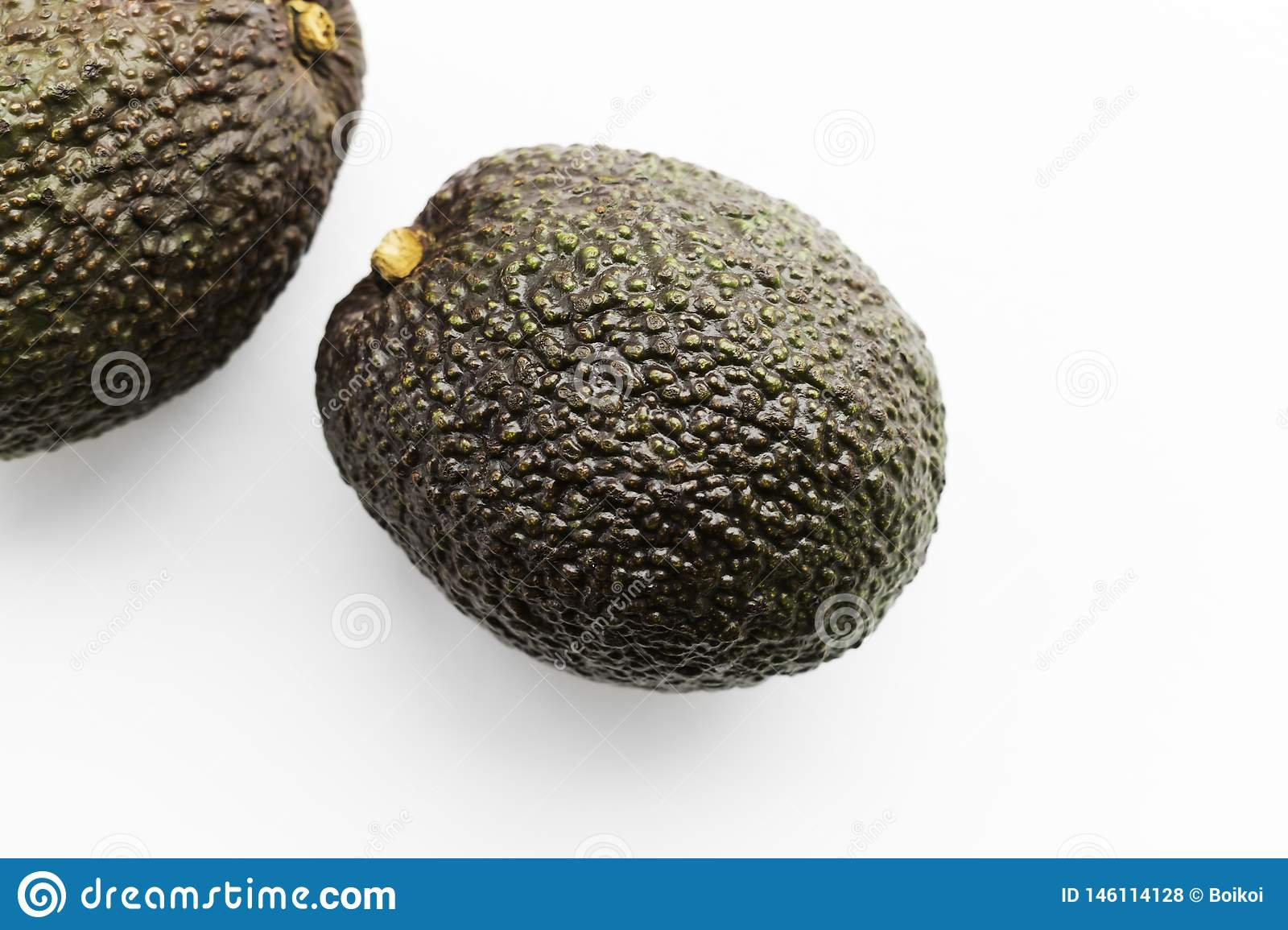 Two ripe avocados Haas on a white background